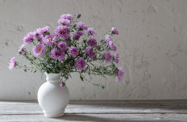 Violet flowers in white vase on old wall