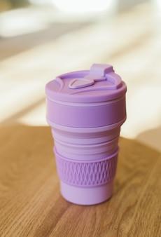 室内の廃棄物ゼロのスタイルでプラスチックなしの飲み物用の紫の折りたたみ式シリコンカップ、クローズアップ。
