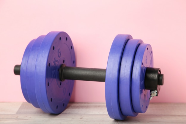 Violet gym dumbbell on pink background