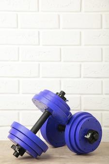 Violet gym dumbbells on white brick wall