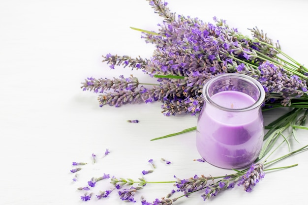 Violet lavender flowers and lavender aromatic candle in the glass jar.