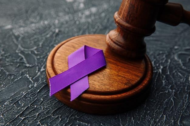 Фиолетовая лента и молоток на сером