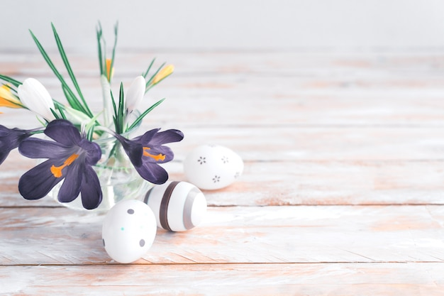 Violet spring flowers in vase and easter eggs on white wooden table