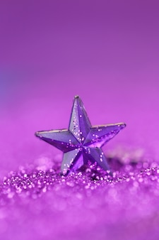 Violet star on a lilac glitter background on a blurry purple background