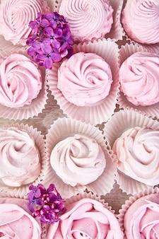 Фиолетовый сладкий домашний зефир из черной смородины возле сиреневых цветов