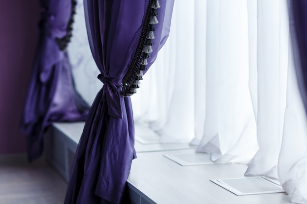 Violet trendy curtains along window with a wide sill