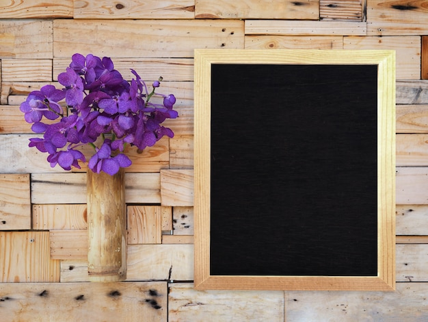 Violet vanda orchid in bamboo vase and blank menu board hanging on wooden plank wall.