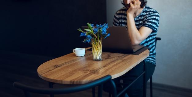 Фиалки и кофейная чашка на деревянном столе против человека, который работает на ноутбуке.