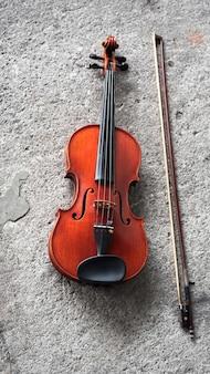 Скрипка и смычок на первом этаже цемента поверхности гранж, показать деталь акустического инструмента