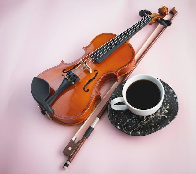 Скрипка и смычок рядом с белой керамической чашкой с черным кофе. на фоне