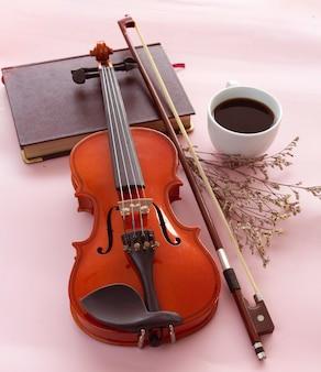 Скрипка и смычок рядом с белой керамической чашкой с черным кофе на пастельном фоне