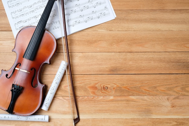 Скрипка и ноты на деревянном столе