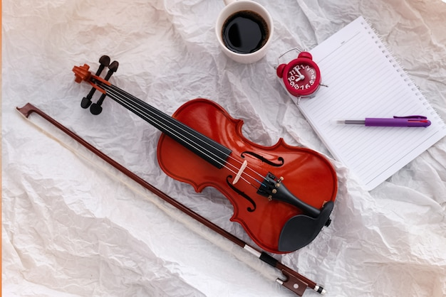Violin and bow put beside red alarm clock, book and coffee cup, on grunge surface