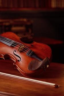 レトロなスタイルのバイオリンと木製のテーブルの弓、誰も。クラシック弦楽器、音楽芸術、古いビオラ
