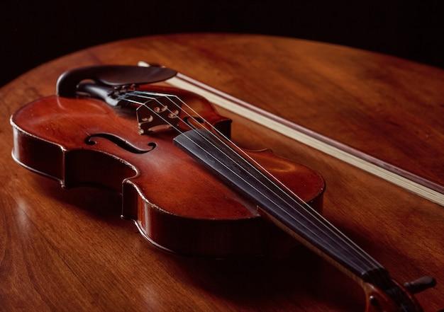 Скрипка в стиле ретро и смычок на деревянном столе, никто