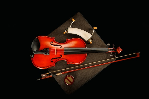 Violin on its special box with its bow on a black