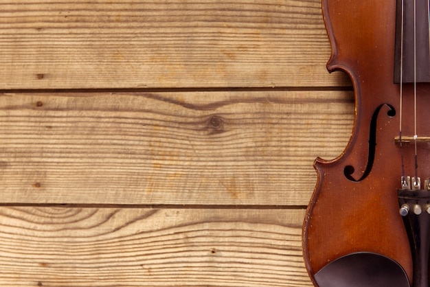 Violin lies on a wooden table background