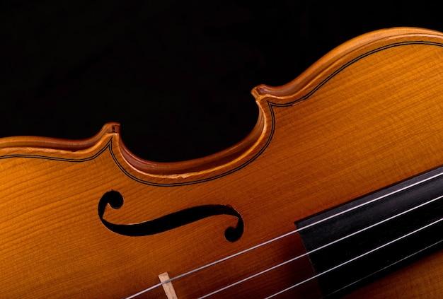 黒に分離されたオーケストラのクローズアップのバイオリン楽器