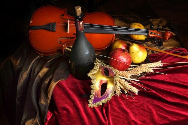 テーブルの上の古いワインと熟した果物のボトルの横にあるバイオリン、赤いベルベットのテーブルクロス、劇場用マスク
