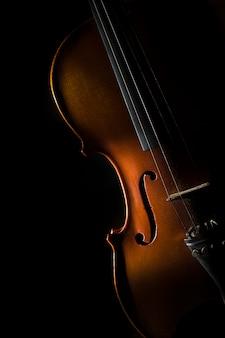 한쪽에 비스듬한 빛에 검은 배경에 바이올린