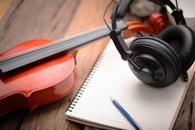 Violin orchestra instrumental over  wooden background