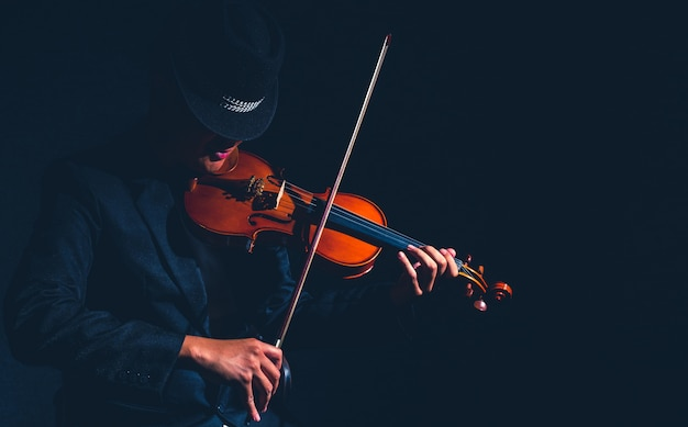 Violin player in dark studio, musical concept