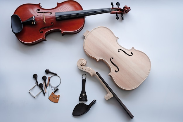 Violin put beside completed violin on white background