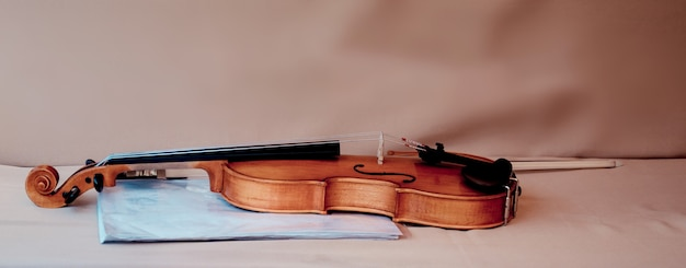 Violin with bow and blue folder for music sheets on table