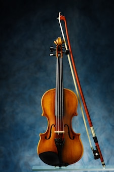 Violin with bow on blue wall.