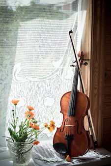 Violin with sheet music and flowers on windows.