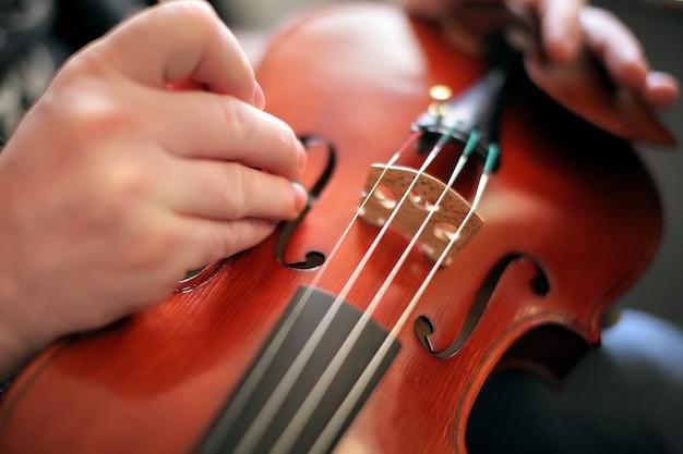 Violinist adjusts the violin