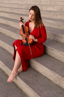 Violinist posing on steps with violin