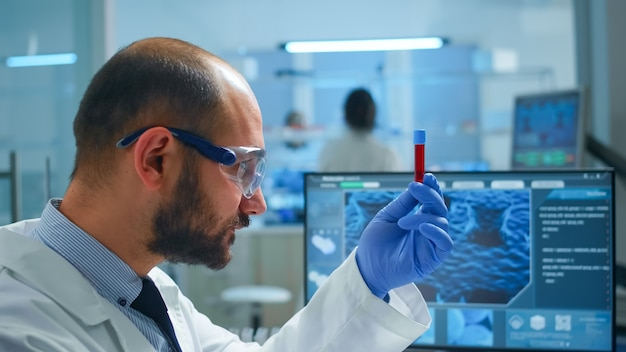 Viorolog researcher examining blood sample from test tube working in modern equipped laboratory