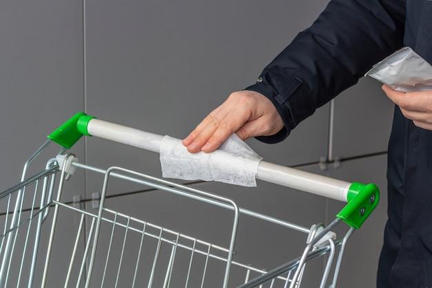 바이러스 성 질병 예방 개념. 남자는 쇼핑몰이나 슈퍼마켓에서 소독 촉촉한 수건으로 공공 쇼핑 카트 핸들을 정리합니다. 전염병 중 코로나 바이러스 예방, 안전 규칙