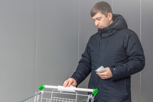 바이러스 성 질병 예방 개념. 남자는 쇼핑몰이나 슈퍼마켓에서 소독 촉촉한 수건으로 공공 쇼핑 카트 핸들을 정리합니다.