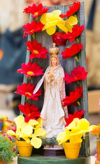 Virgin mary statue figure with red flowers and yellow clay pots around her catholic religion symbol