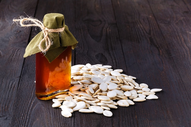 Virgin pumpkin oil in small bottle on wood table