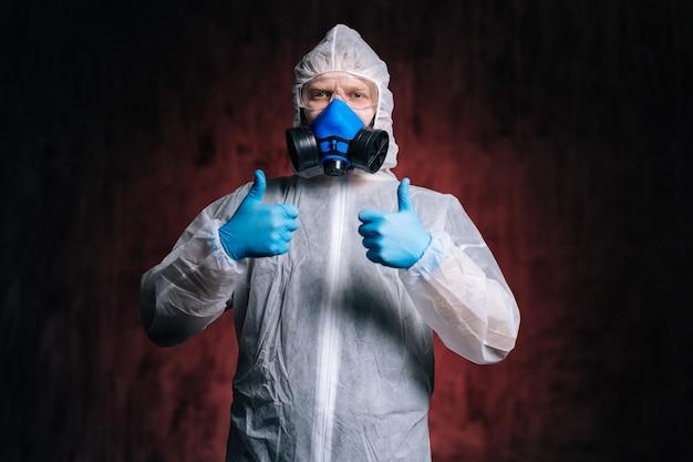 위험 물질 고글과 인공 호흡기를 쓴 바이러스 학자가 두 번 엄지 손가락 제스처를 보여주고 있습니다