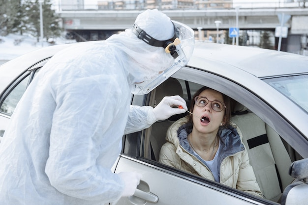 A virologist or medical doctor wearing ppe hazmat protective clothing takes a sample of a pcr test with a cotton swab