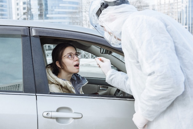 A virologist in a ppe protective suit, mask, gloves makes a smear or test with a cotton swab for coronavirus covid-19 to a car driver