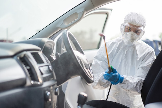 Virologist scientists wearing ppe kits are cleaning the virus in cars.