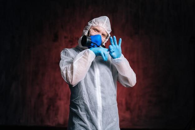 유해한 고글과 호흡기를 착용한 바이러스 학자가 불쾌한 제스처를 보여줍니다.