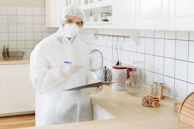 Virologists carry out professional cleaning with the help of a disinfectant or gas, household, apartment equipment.