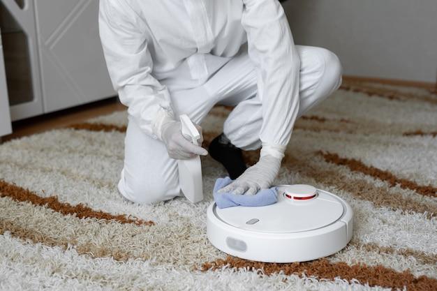 Вирусологи, люди в защитных костюмах проводят дезинфекцию в квартире.