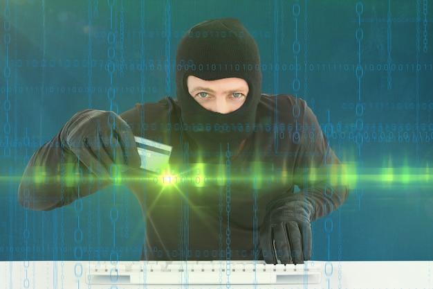 Virtual criminal with credit card and keyboard Free Photo