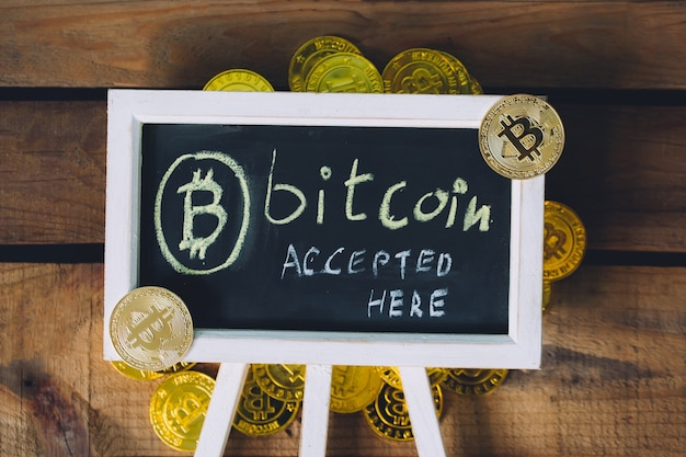 Virtual currency bitcoin accepted here sign over wooden background with real bitcoins