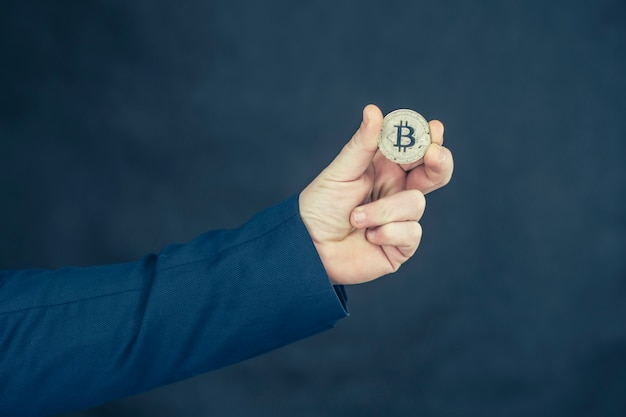 Virtual currency and blockchain concept. businessman in a blue jacket holding bitcoin in his hands.