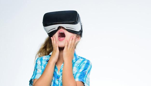 学校の生徒のための仮想教育。仮想体験を取得します。バーチャルリアリティの概念。白い背景の上のヘッドマウントディスプレイを持つ女の子かわいい子。小さな子供は現代のテクノロジーバーチャルリアリティを使用しています。