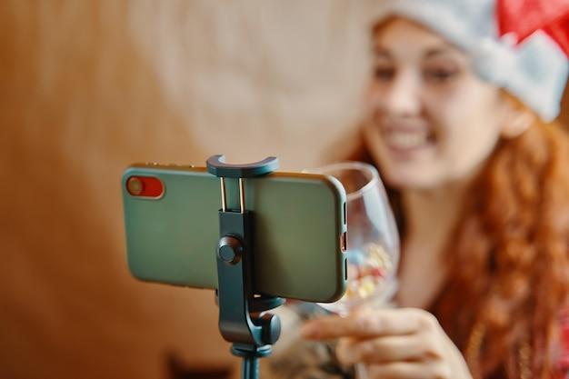 友人の同僚への仮想挨拶とスマートフォンの赤毛の女の子を介したビデオ会議の使用...