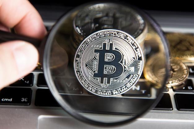 Виртуальные деньги серебряный биткойн под увеличительным стеклом